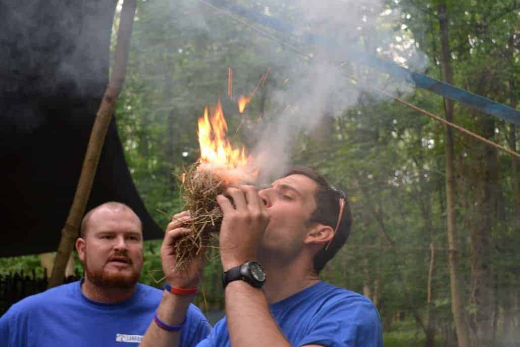 Wildway Bushcraft Owner John blowing an ember into fire